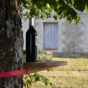 StammTisch. Ein Holztisch mit Spanngurt befestigt an einem Baumstamm zum abstellen von Getränken