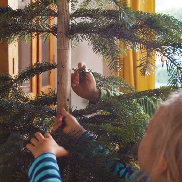 Der Keinachtsbaum wird mit Tannenzweigen geschmückt.